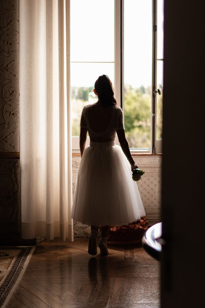 Jeune mariée regardant par la fenêtre lors des préparatifs de son mariage à Castelginest